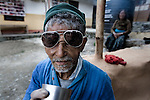 "An elderly man drinks tea at an ""Aged Shelter"" in Pokhara, Nepal, a place for seniors to live who have no other family members to look after them. The shelter has no running water, cooking is done over a fire because they can not afford to buy gas for a stove, there are no nurses or doctors available, no heating, and no medication."