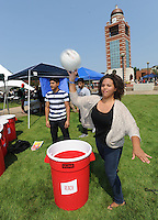 NWA Democrat-Gazette/ANDY SHUPE<br /> Shanda Brown (right) throws a volleyball Wednesday, Aug. 26, 2015, beside Luis Murcia (center) and Henry Araujo, all freshmen at the University of Arkansas-Fort Smith, while playing an oversized game of pong with friends at the Grand Avenue Baptist Church booth during the Campus Picnic and Block Party on the campus green at UAFS in Fort Smith. Classes began for the fall semester Aug. 17 and the university held the event to make students familiar with clubs and services that are available to them.