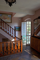 The landing has a carved wooden balustrade and stone tiled floor