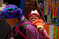Tibetan woman carrying child on the Barkhor pilgrim circuit around the Jokhang Temple, Lhasa, Tibet.