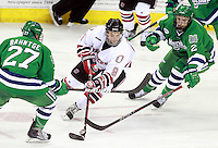 Nebraska Omaha's James Polk works the puck between Mercyhurst's Daniel Bahntge and Nick Jones.  (Photo by Michelle Bishop) ..