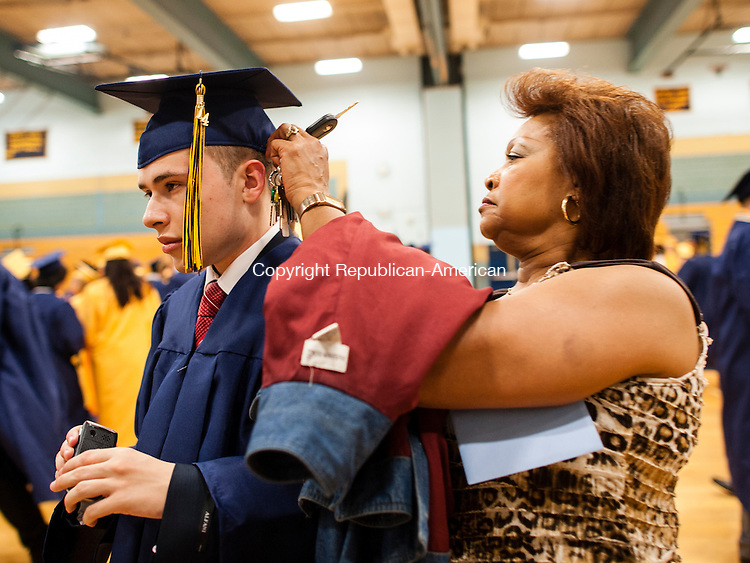 WATERBURY, CT-17 June 2014-061714EC13-  Audrey Whidbee, a paraprofessional at Kennedy High School, helps Pasquale Barone with his cap and gown before graduation Tuesday night. Erin Covey Republican-American