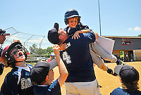 After getting the game winning hit with the pressure on in the bottom of the last inning to win the game, 8 year old Cole Western leaped into his dad Matt Western's arms as his dad and the whole team rushed out onto the field to celebrate the  Fauquier Gators dramatic 14-13 win in their Cal Ripkin League district playoff game at the FHS softball field Saturday morning in Warrenton, VA.