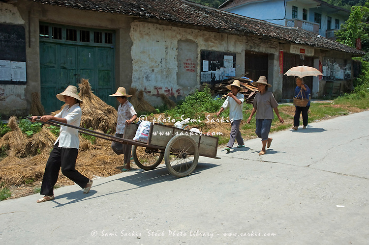 Shoppers carrying goods back on a chariot from the Fuli village weekly market, Guangxi, China.