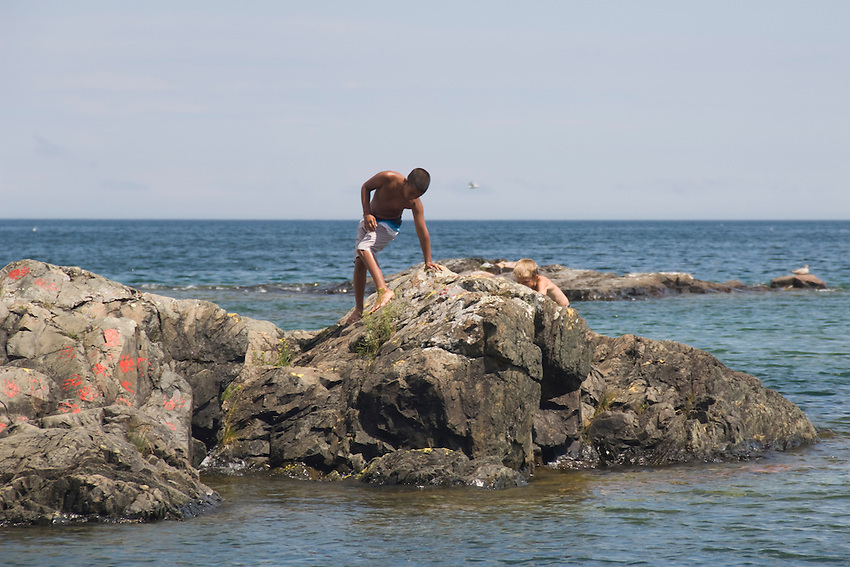 A boy explores a rocky island at McCarty Cove beach on Lake Superior in Marquette Michigan.
