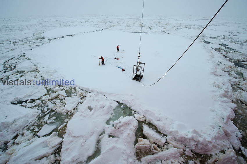 Scientists measuring and collecting samples from an ice floe off a research ship, Bering Sea.