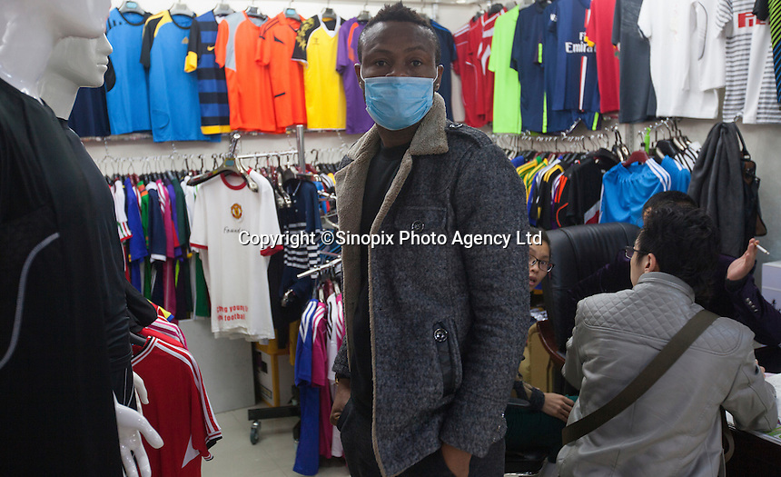 An African man wears a surgical face mask fro protection in an area of Guangzhou known to locals as 'Chocolate City', Guangzhou, Guangdong Province, China, 08 December 2014. The health authorities of Guangzhou are said to be stepping up their monitoring of the African community in light of the ongoing outbreak of the Ebola virus disease in West Africa.