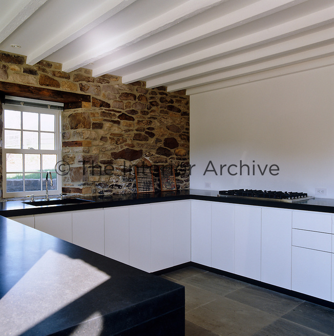 The modern white lacquered kitchen units and granite worktop were designed to create a linear uniformity