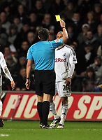 Pictured: Jazz Richards of Swansea (R) sees a yellow card by match referee Lee Probert (L). Tuesday 27 December 2011<br />