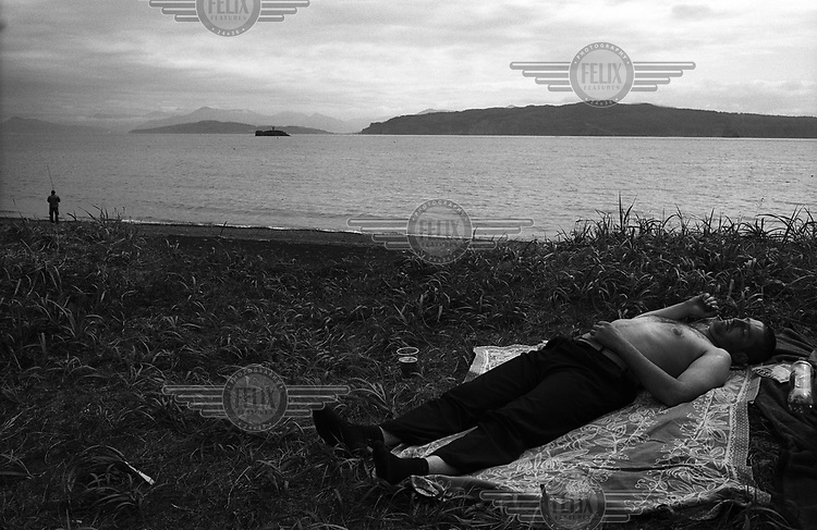 A man rests on a cloth on the seashore on the Avach Gulf while another man fishes in the distance.