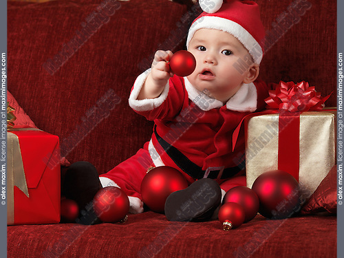 Six month old baby boy wearing Santa Christmas costume and holding a red bauble in his hand