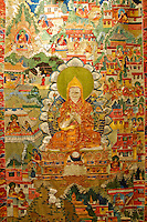 Ancient silk-embroidered thangka of the life of Tsongkhapa, 1357-1419, founder of the Gelugpa order of Buddhism in Tibet.  He wears the characteristic yellow hat, hands held in the teaching mudra, flanked by two lotus blossoms, Tibet Museum, Lhasa, China.