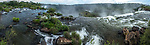 A panoramic image of the Iguazu River flowing over the precipice of the San Martin Waterfall in Iguazu Falls National Park in Argentina.  A UNESCO World Heritage Site.