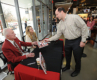 "STAFF PHOTO ANDY SHUPE - Nathan Harris of Fayetteville, right, shakes the hand of Frank Broyles, former coach and director of athletics at the university, Friday, Dec. 12, 2014, as Broyles' granddaughter Molly Arnold Gay assists after Harris had a copy of the book, ""An Arkansas Legend: The Life & Legacy of Frank Broyles,"" autographed during a book signing at the University Bookstore on the University of Arkansas campus in Fayetteville. Ten percent of the proceeds from sales of the boo, which was published by NWA Media and the Arkansas Democrat-Gazette, will be donated to the Frank and Barbara Broyles Foundation: Care Givers United for Alzheimer's and Dementia. Broyes, 89, will take part in another event to sign limited-edition footballs celebrating the 50th anniversary of the 1964 National Championship season Wednesday at 2:30 p.m. at the Bank of Fayetteville with all proceeds benefitting the foundation."