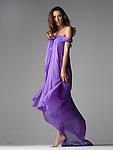 Beautiful brunette fashion model barefoot in purple gown