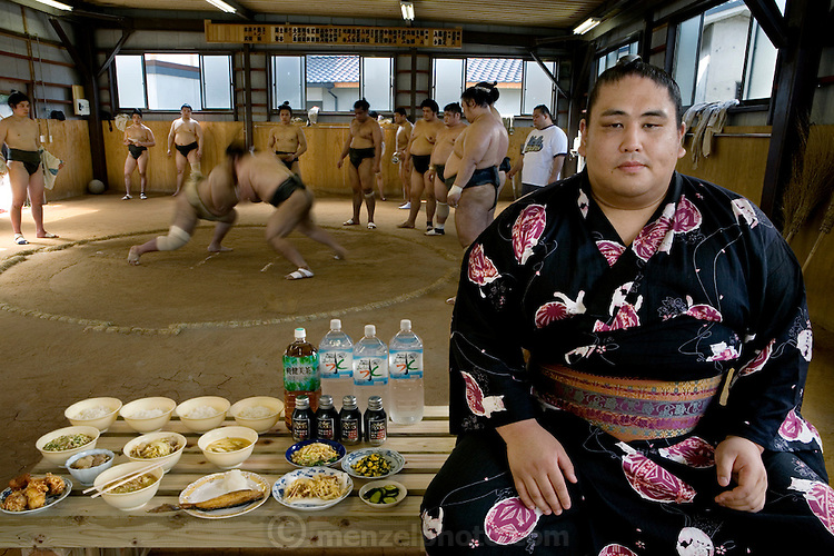 "Takeuchi Masato, a professional sumo wrestler whose ring name is Miyabiyama (meaning ""Graceful Mountain""), with his day's worth of food in the team's practice ring in Nagoya, Japan. (From the book What I Eat: Around the World in 80 Diets.) MODEL RELEASED."