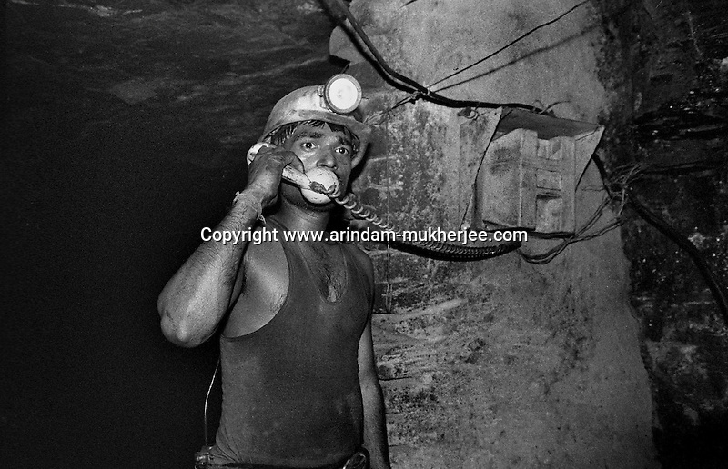A miner using the intercom (the only way of communication from 5 kms and 450mts below the surface) to communicate with the outside, at an inclined mine of North Searsole Coliery in Ranigunj, West Bengal, India. Arindam Mukherjee