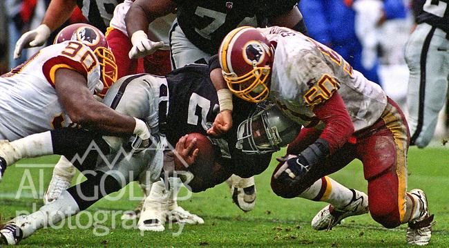 Oakland Raiders vs. Washington Redskins at Oakland Alameda County Coliseum Sunday, November 29, 1998.  Redskins beat Raiders  29-19.  Washington Redskins defensive end Kenard Lang (90) and linebacker Derek Smith (50) stop Oakland Raiders running back Napoleon Kaufman (26).