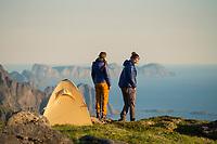 Two female hikers stand near tent on mountain summit, Moskenesøy, Lofoten Islands, Norway