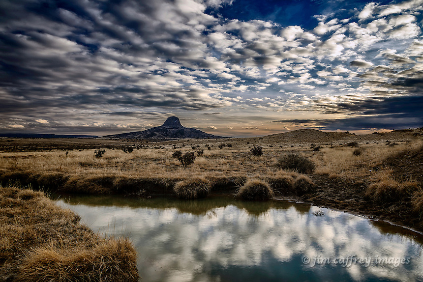 A small pond in the Rio Puerco Valley at twilight with Cabezon Peak in the distance.