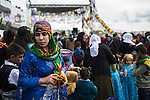 A woman wearing traditional Kurdish clothing and a scarf using the Kurdish colors green, yellow, and red, at Newroz, the Kurdish New Year celebration, in Viranşehir, Turkey, March 18, 2015. Newroz, or Nowruz, is an ancient holiday celebrated by a multitude of ethnic groups across Iran, Central Asia, and the Caucuses, and ushers in the first day of Spring, March 21. For Kurds, Newroz is a means of political and cultural expression, featuring Kurdish politicians, activists, and musicians, and has become a manifestation of Kurdish identity. In Turkey, the celebrations begin a few days before the Vernal Equinox, culminating in a huge gathering in the heart of Turkey's Kurdish population, the southeastern city of Diyarbakir. This year, PKK founder Abdullah Öcalan, who despite serving a life sentence for treason still enjoys widespread influence among Kurds, sent a letter that was read at Newroz in Diyarbakir, calling for an end to the PKK's armed struggle against the Turkish state.