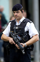 Armed policeman wearing flak jacket and with machine gun, London, England, UK