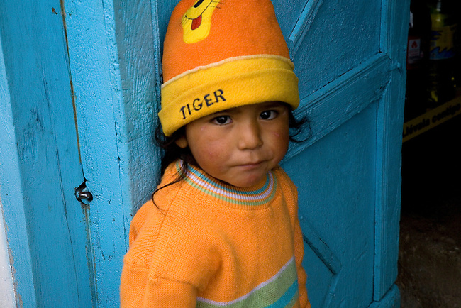 A YOUNG PERUVIAN BOY STANDS IN A DOORWAY IN MOLLEPATA