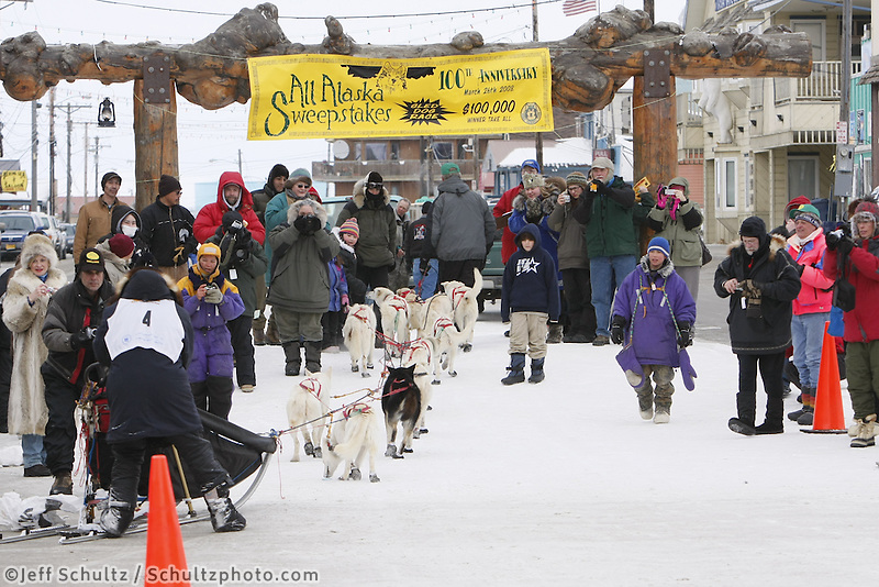 Jim Lanier crosses the finish line on Front Street  in 6th place in the  2008 All Alaska Sweepstakes Sled Dog Race, Alaska.