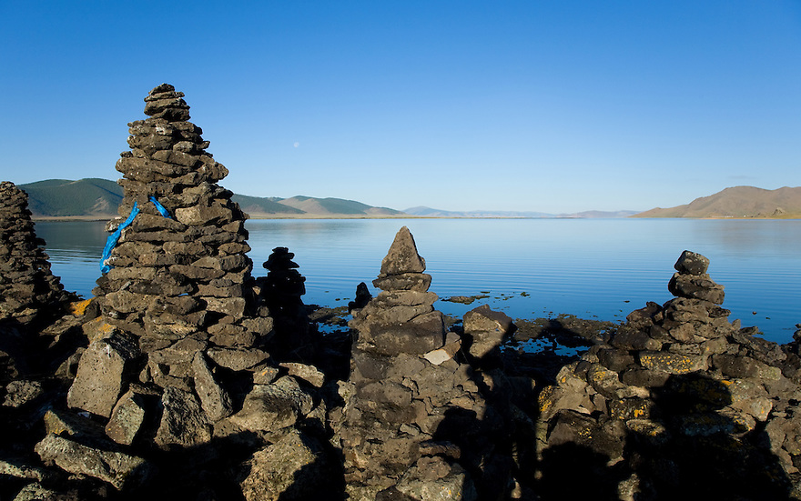 Terkhiin Tsagaan Nuur (Great White Lake) Mongolia..Volcanic rocks stacked by Mongolian people. Blue silk ribbons to bring good luck.