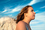 Closeup of girl wearing angel wings, hair blowing in wind, on Long Island, New York, USA