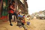 A police man and shoeshine boy on a street in Ixcan, Guatemala - a rough, dusty border town with Mexico.