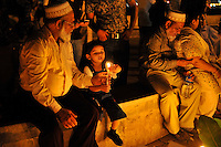 A young boy lights a candle during a remembrance vigil next to Taj Mahal Hotel in Mumbai on the  30th of November, 2008, Mumbai, India.