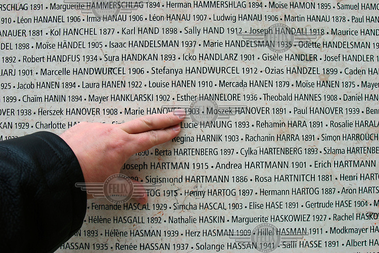 A person points out a name carved on the Paris Shoah Memorial wall that lists the names of French Holocaust victims.