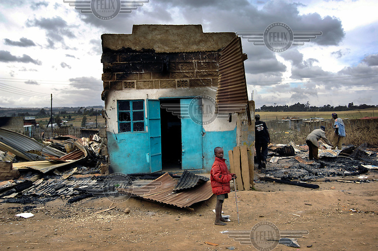 A small boy stands next to a destroyed shop in Mau-Summit, a small trading centre not far from Nakuru. During ethnic clashes it was razed to the ground by Kalenjin warriors who were fighting with the Kikuyu traders. Ethnic violence sparked last December following protests against disputed election results, after suspected vote rigging by Kikuyu President Mwai Kibaki...