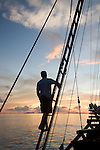 A man silhouetted in the rigging of a Phinisi schooner at sunset, Raja Ampat, West Papua, Indonesia, Pacific Ocean