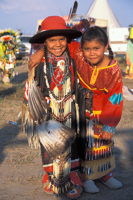 Two young pow wow buddies dressed in traditional regalia are arm in arm at a pow wow both dressed in traditional regalia