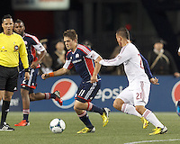 New England Revolution midfielder Kelyn Rowe (11) works to clear ball as Real Salt Lake midfielder Luis Gil (21) defends. In a Major League Soccer (MLS) match, Real Salt Lake (white)defeated the New England Revolution (blue), 2-1, at Gillette Stadium on May 8, 2013.