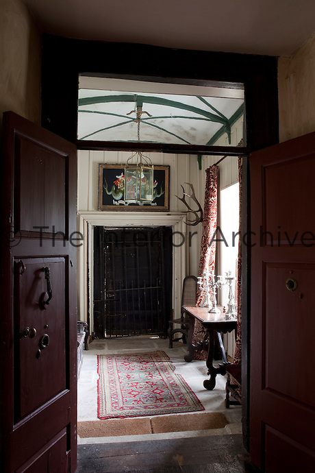 Double doors open onto a narrow stone-flagged hallway and a small Jacobean entrance door