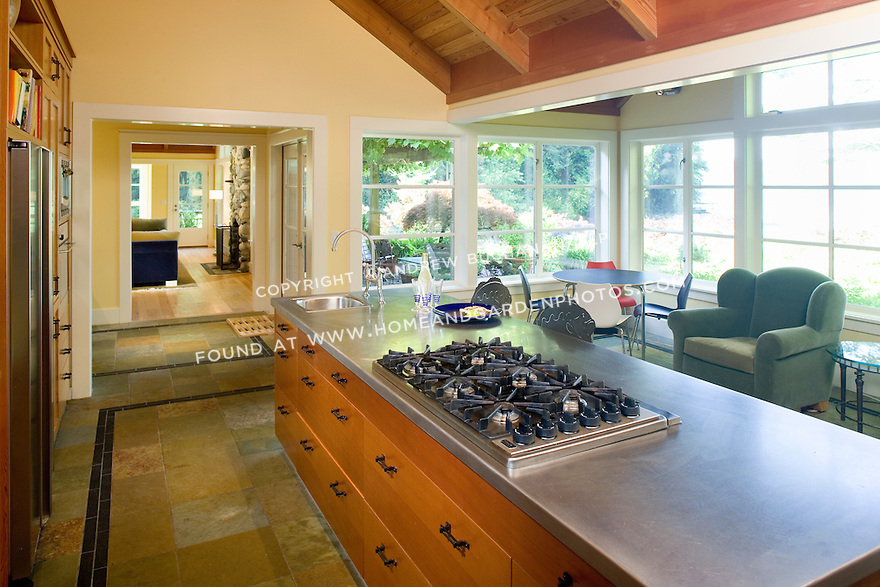 6 burner gas range emmbedded in a stainless steel-topped island in the kitchen of a waterfront weekend vacation retreat on Washington State's Vashon Island