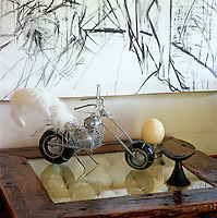 A model of a motorbike sits on the glass top of the coffee table that houses a collection of ostrich eggs