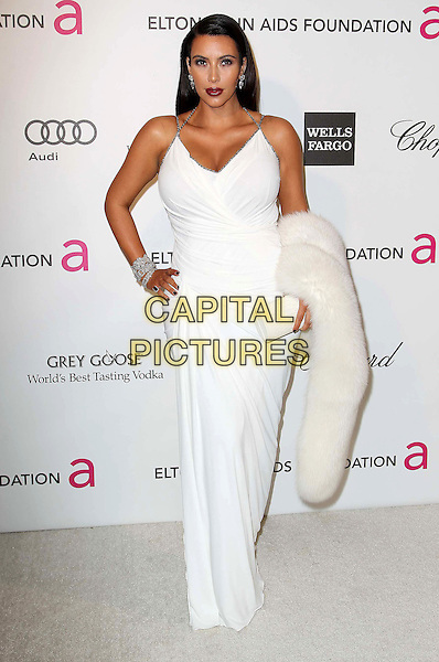 KIm Kardashian.The 21st Annual Elton John AIDS Foundation Academy Awards Viewing Party held at The City of West Hollywood Park in West Hollywood, California, USA..February 24th, 2013.oscars full length white sleeveless dress carrying fur pregnant diamond bracelet halterneck hand on hip clutch bag.CAP/ADM/KB.©Kevan Brooks/AdMedia/Capital Pictures.