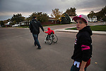 Mitchell Baalman, left, walks with two of his three sons,  Tucker, center, 7, and Aidan, right, 10, to the high school football game in Hoxie, Kan. on Friday, Oct. 12, 2012. As historically dry conditions continue, farmers from South Dakota to the Texas panhandle rely on the Ogallala Aquifer, the largest underground aquifer in the United States, to irrigate crops. After decades of use, the falling water level ? accelerated by historic drought conditions over the last two years ? is putting pressure on farmers to ease usage or risk becoming the last generation to grow crops on the land. Farmers like Mitchell Baalman and Brett Oelke (not pictured) are part of a farming community in in Sheridan County, Kansas, an agricultural hub in western Kansas, who have agreed to cut back on water use for crop irrigation so that their children and future generations can continue to farm and sustain themselves on the High Plains.