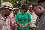 Fishing Cat (Prionailurus viverrinus) biologists, Anya Ratnayaka and Maduranga Ranaweera, showing fishing cat pictures to wetland neighbors, Urban Fishing Cat Project, Diyasaru Park, Colombo, Sri Lanka