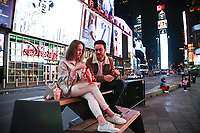 NEW YORK, NY - MARCH 19:  A man and a woman are sitting in Time Square on March 19, 2020 in New York City. Gov Cuomo has ordered nonessential businesses in the state to close by 8 p.m. Sunday as more than 11,000 confirmed cases and 56 deaths. (Photo by Pablo Monsalve / VIEWpress via Getty Images)