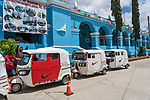 Mototaxis parked in front of the city hall or municipal palace of Tlacochahuay de Morelos, Mexico.