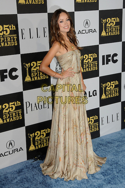 OLIVIA WILDE.25th Annual Film Independent Spirit Awards - Arrivals held at the Nokia Event Deck at L.A. Live, Los Angeles, California, USA..March 5th, 2010.full length strapless beige gold print printed patterned pattern dress hand on hip maxi.CAP/ADM/BP.©Byron Purvis/AdMedia/Capital Pictures.