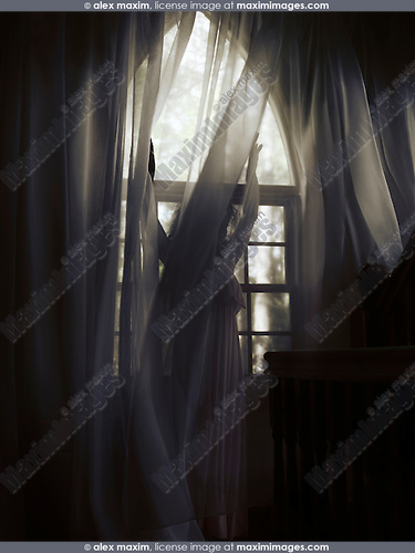 Artistic dramatic photo of a young woman in a dress standing behind the curtain by a window in a dark room of a house