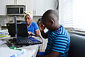 MIRAMAR, FL - MARCH 31: Broward County Kindergarten teacher Lisa in front of her laptops with her student and helping her son Jordan with his class during distance virtual school learning amid Coronavirus Pandemic in Broward County, Florida Public Schools. Florida began their experience with online virtual distance learning, amid the growing coronavirus (COVID-19) pandemic on March 31, 2020 in Miramar, Florida.   ( Photo by Johnny Louis / jlnphotography.com )
