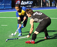 Malaysian captain Mohd Madzli Ikmar Mohd Nor flicks the ball past Simon Childs during the international hockey match between the New Zealand Black Sticks and Malaysia at Fitzherbert Park, Palmerston North, New Zealand on Sunday, 9 August 2009. Photo: Dave Lintott / lintottphoto.co.nz