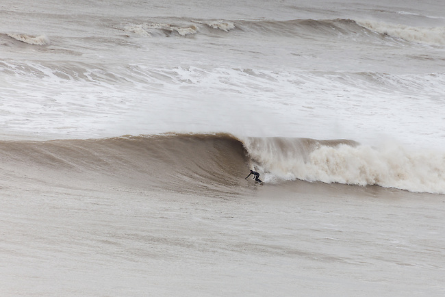 Surfers enjoying a big swell hitting the coast at Freshwater Bay on the  Isle of Wight.